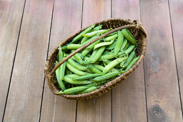 Basket with peas/Basket with peas on wooden background