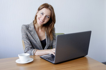 Cute young female adult working on laptop computer at desk next to coffee cup