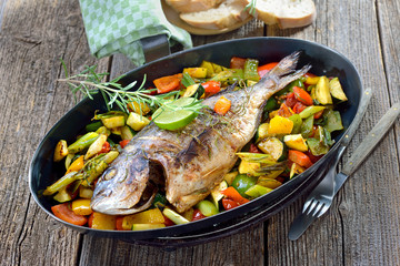 Mediterrane Küche: Gebackene und übergrillte ofenfrische Rosmarin-Dorade royal auf gemischtem Ofengemüse mit Olivenöl - Oven fresh gilthead seabream baked with rosemary on mixed summer vegetables