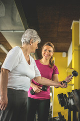 Personal trainer working exercise with senior woman in the gym. Woman picking weight. Workout in gym