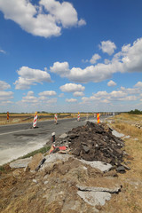 Damaged asphalt road and small bridge in reconstruction with blue sky and clouds