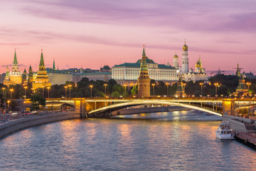 Illuminated Moscow Kremlin and Moscow River with bridge in the summer evening. Pink sky. Russia
