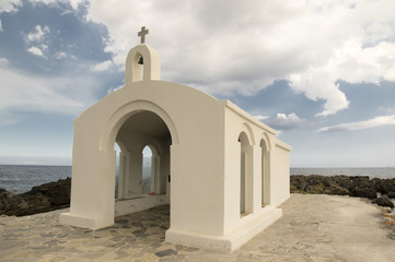 Saint Nicholas small church, amazing white chapel abandoned in the sea on the stones and rocks