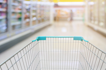 Shopping cart view with milk and yogurt product shelves aisle in supermarket