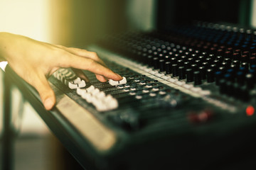 Close up hands of sound engineer working at mixing panel in recording studio. Vinatge or retro tone.