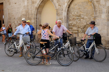 Tourists with bicycles listen to a tour guide during a visit in the Old Town of Valencia