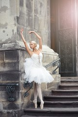 Attractive young female ballet dancer performing outdoors dancing on the stairway of an old fashioned building.