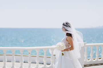 Beautiful brunette bride on a walk by the sea