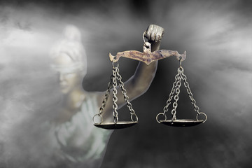 Lady Justice or Themis (God of Justice) raising the Scale of justice through fog (Concept of hope in justice)