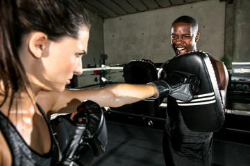 Woman trainee with screaming motivating male trainer throws powerful punch at practice pad