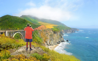 Beautiful summer coastal landscape,  Man on hiking trip resting on top of the mountain looking at view and taking pictures with phone.. Pacific Ocean, Big Sur, California, USA