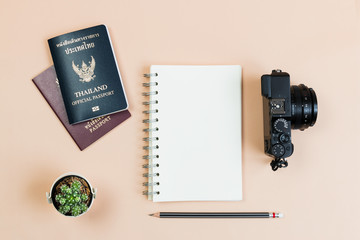 Flat lay empty book and pencil for design work with vintage digital compact camera, Thailand official passport and smart phone and small cactus on yellow pastel color background.