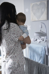 Caucasian mother holding baby son near crib