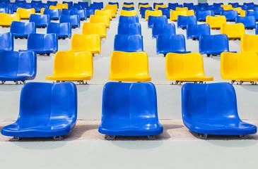 Foto op Plexiglas Stadion Rows of empty blue and yellow plastic seats in public sport stadium