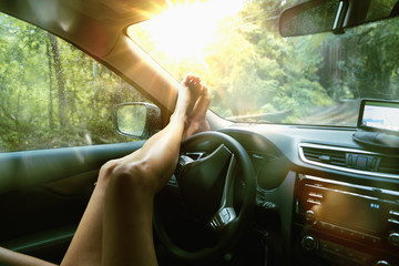Legs of Caucasian woman on car dashboard