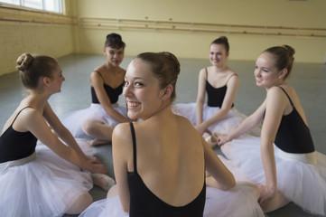 Portrait of smiling girl sitting on floor in ballet studio