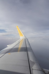 Cloudy sky from an airplane window with a grey wing with yellow flap