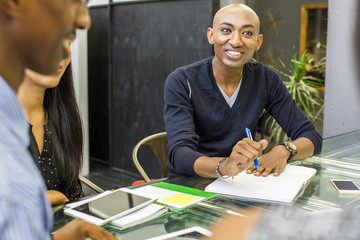 Smiling man with notebook in meeting