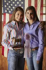 Twin Mixed Race teenage girls posing with awards near American flag