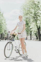 Portrait of Middle Eastern woman holding bouquet and bicycle