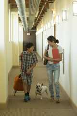 Asian mother and son in corridor with dog