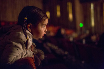 Mixed Race girl leaning on chair watching movie in theater