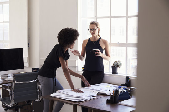 Two young businesswomen discussing work in an office