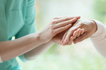 Caretaker massaging pensioner's hand