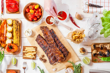 Spicy hot grilled spare ribs from a summer BBQ served with chips, corn and fresh tomatoes on an old wooden cutting board, top view