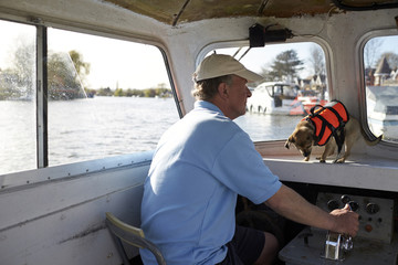 Mature man with his pet dog driving a boat in river