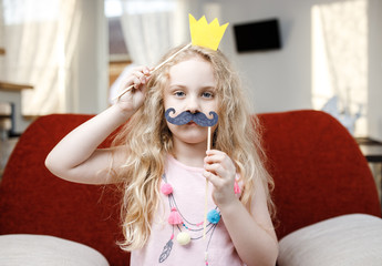 Cute little girl with paper crown and mustaches while sitting on red chair at home.