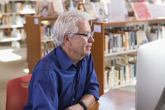 Smiling Hispanic man using computer in library