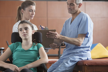Caucasian doctor and nurse with frustrated girl in wheelchair
