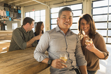 Portrait of smiling couple drinking beer with friends in brew pub