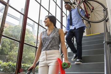 People carrying bicycle and skateboard on staircase