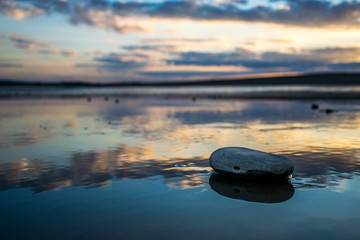 Solitary pebble on wet sand reflecting sunset sky colours.