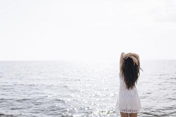 Middle Eastern woman standing near ocean