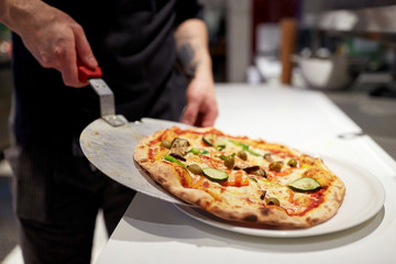 Tuinposter Pizzeria cook with baked pizza on peel at pizzeria