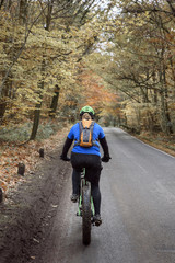 Caucasian woman riding bicycle on forest road