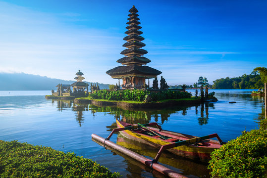 Pura Ulun Danu Bratan, Hindu temple with boat on Bratan lake landscape at sunrise in Bali, Indonesia.