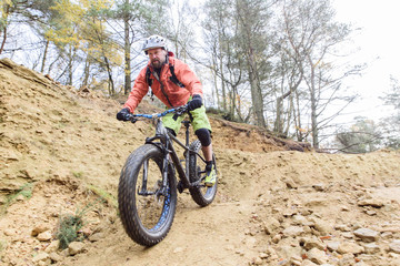 Caucasian man descending dirt trail on bicycle