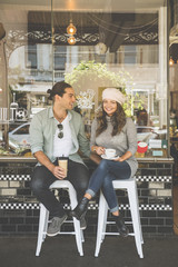 Couple sitting on stools outside coffee shop