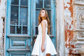 Beautiful girl in a white dress near a blue door