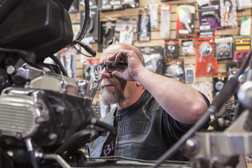 Caucasian man repairing motorcycle adjusting eyeglasses