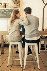 Smiling Caucasian woman leaning on man in coffee shop