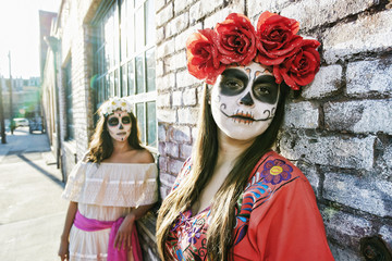 Women on sidewalk wearing skull face paint