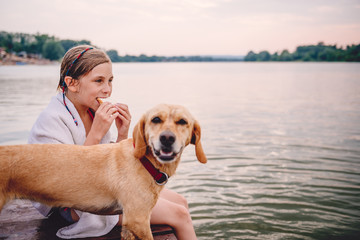 Girl eating sandwich by the river