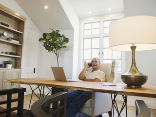 Caucasian man talking on cell phone in home office