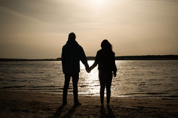 Boy and girl standing in sunset together in hands near river.