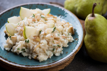 Close-up of pear risotto served on a turquoise plate, selective focus
